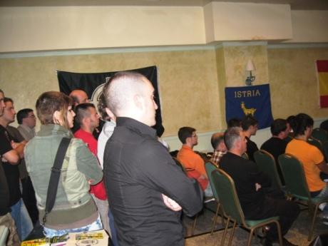 Al final de la sala, tanto a derecha como a izquierda, los asistentes en pie escuchan las conferencias.